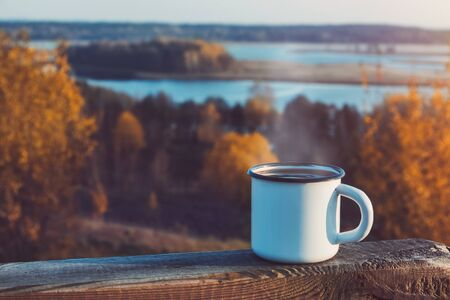 Enameled cup of coffee or tea on autumn landscape outdoors. Standard-Bild
