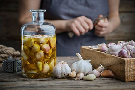 Garlic aromatic flavored oil or infusion bottle and wooden crate of garlic cloves on wooden kitchen table. Woman peels garlic with a knife on background.