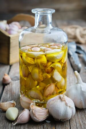 Garlic aromatic flavored oil or infusion bottle and garlic cloves.  Reklamní fotografie