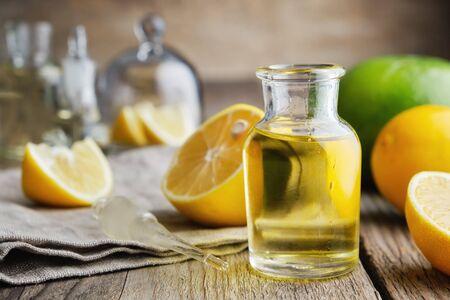 Bottle of citrus lemon essential oil and citrus fruits on table. Stock Photo