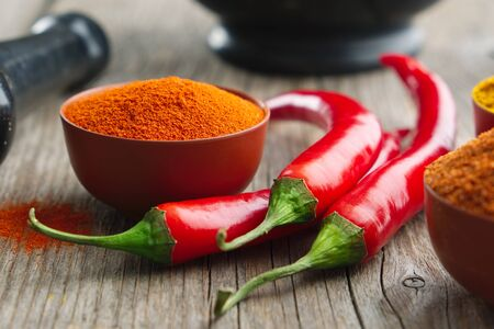 Whole and ground to powder red chili pepper. Mortar and pestle.