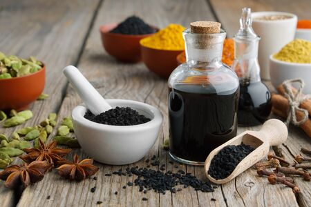 Black cumin or roman coriander seeds, black caraway oil bottles and aromatic spices and herbs