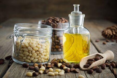 Pine nuts essential oil bottle and jar of cedar pine nuts.
