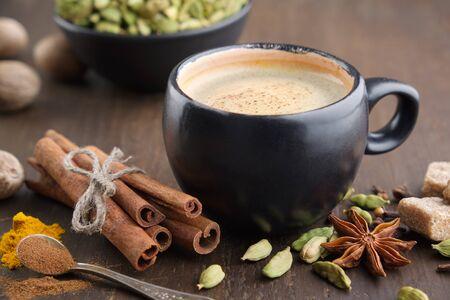 Filiżanka kawy z przyprawami. Laski cynamonu, kardamon, ziele angielskie, kurkuma i anyż na drewnianym stole.