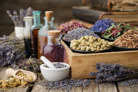 Bottles of healthy tincture or infusion, mortar and bowls of medicinal herbs in wooden crate, stack of old books on background. Herbal medicine.