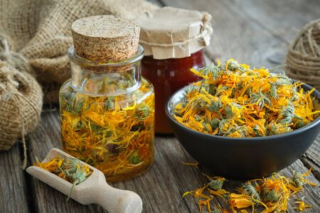 Bottles of calendula infusion or oil, healthy marigold flowers in bowl and calendula salve on wooden table. Herbal medicine.