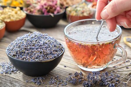 Healthy lavender tea cup being stirred by a woman hand, on a wooden table