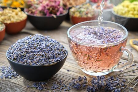 Healthy lavender tea cup being stirred by a woman hand, on a wooden table top Фото со стока - 145315135