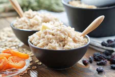 Bowls of healthy oatmeal porridge with dried apricots and raisins. Фото со стока - 146050529