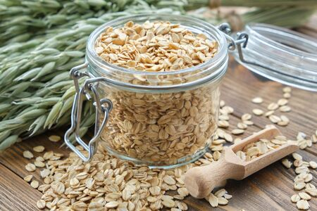Jar of oat flakes and green oat ears on wooden table.