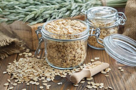 Jars of oat flakes, green oat ears and sack on wooden table.