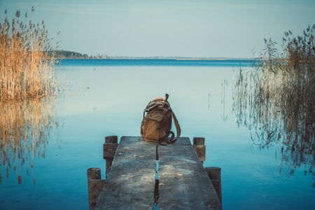 Backpack of traveller on wooden pier on blue summer lake. Фото со стока