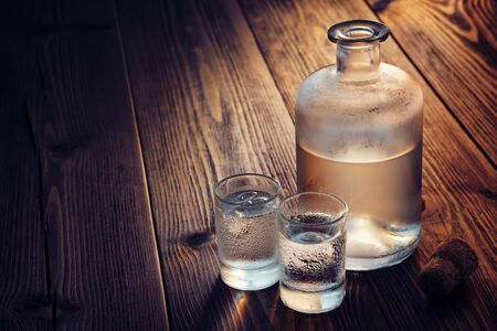 Vodka bottle and two glasses of vodka drink with ice on a wooden table.