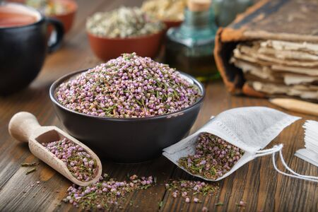 Bowl of dry healthy heather, tea bag with Erica flowers inside. Tea cup, infusion bottle and books on background.