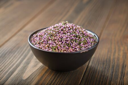 Black bowl of dry healthy heather flowers on wooden table. Фото со стока - 148128019