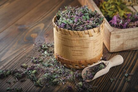 Wooden bowl of dry wild Marjoram or Origanum vulgare plants, wooden crate of medicinal herbs on background.