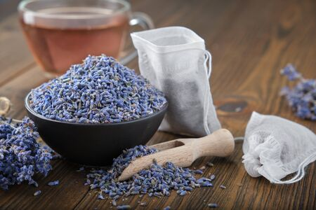 Bowl of dry healthy lavender, tea bag with lavender flowers on wooden table.