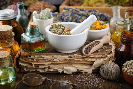 Bottles of healthy infusion or oil, mortars and bowls of medicinal herb and old book on wooden table. Фото со стока - 148128021