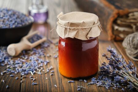 Bottles of lavender salve, balm or cream, healthy lavender flowers, book and essential oil bottle on wooden table. Фото со стока - 148128018