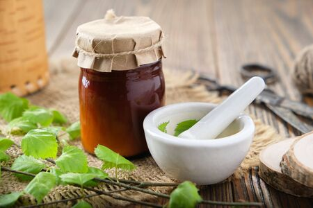Bottle of birch herbal salve, balm or coal tar oil, healthy birch leaves and mortar on wooden table Фото со стока