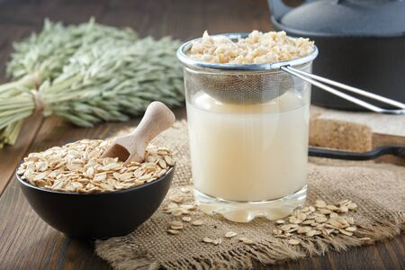 Ingredients and the process of making oats milk or oatmeal beverage at home.  Фото со стока
