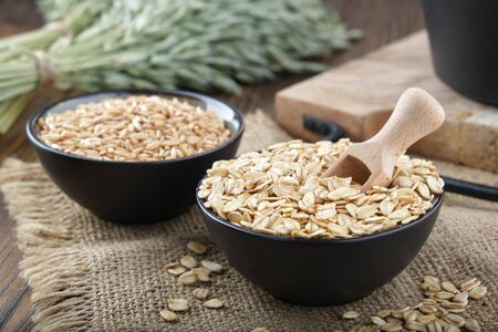 Bowls of oat grains and oat flakes, green oat ears on wooden kitchen table.