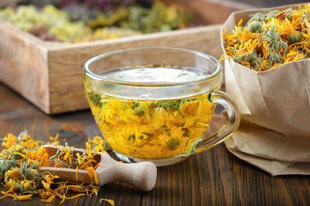 Cup of healthy marigold tea and paper bag of dry calendula flowers. Фото со стока