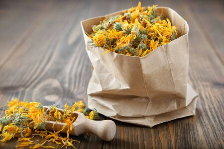 Paper bag of healing calendula) herbs and wooden scoop of dry marigold flowers. Alternative medicine. Фото со стока