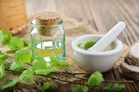 Glass bottle of birch essential oil, herbal infusion or juice. Twigs of Birch tree with leaves, scissors and mortar on table. Фото со стока - 147846740