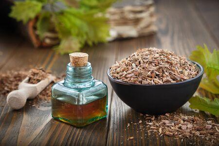 Healthy oak bark in black ceramic bowl, infusion or tincrure bottle, green oak leaves on wooden table.
