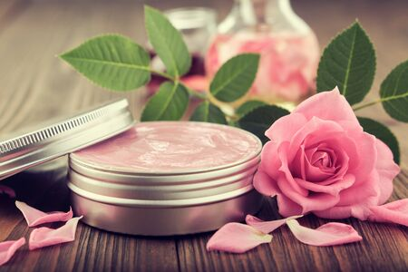 Jar with a homemade moisturizing beauty cream and pink rose flower.  Making of cosmetic products at home. Фото со стока - 149422965