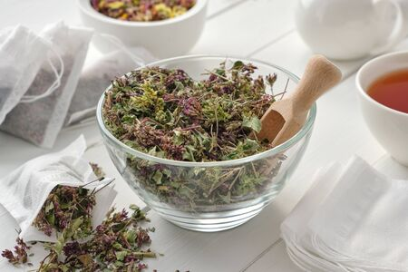 Bowl of dry Origanum vulgare flowers, tea bags filled with wild marjoram flowers. Tea cup and teapot on wooden table. Alternative medicine.