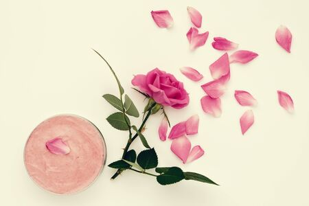 Jar with a homemade moisturizing beauty cream and pink rose flower.  Top view.
