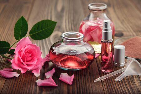 Homemade skin product with flower on wooden table