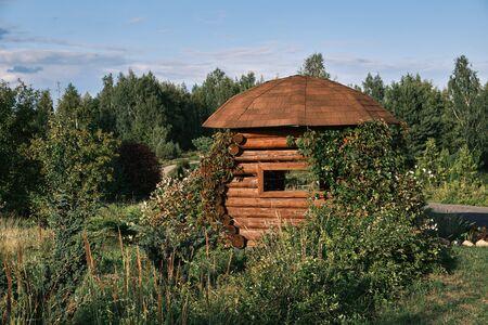 Wooden rustic gazebo in summer park.