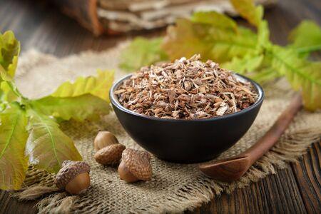 Healthy oak bark in black ceramic bowl, acorns, green oak leaves and old book