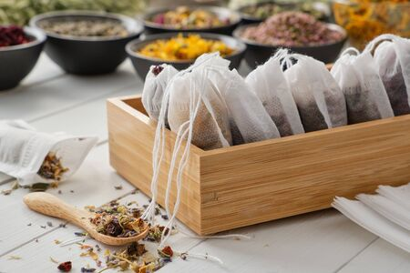 Wooden box of tea bags filled with dry medicinal herbs and flowers. Фото со стока - 149923883