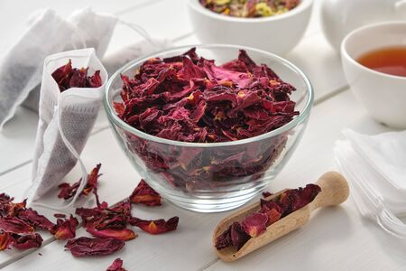 Bowl of dry rose petals, tea bags filled with red petals of healthy rose. Фото со стока - 149923890