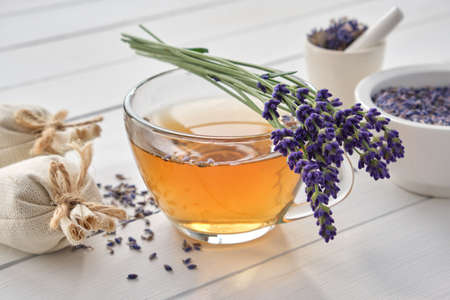 Cup of healthy lavender tea and lavender flowers. Mortars of dry lavender and sachets on background. Alternative medicine.