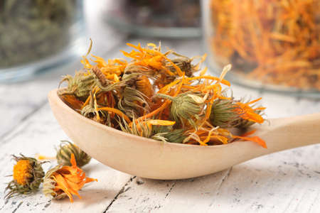 Wooden spoon of dried healthy calendula flowers. Glass jars of dried  marigold petals and medicinal herbs on background. Alternative medicine.