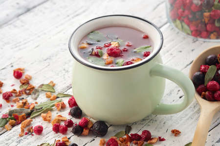 Cup of healthy fruit tea with apples, orange, red and black currant berries. Wooden spoon of dry ingredients for making tea.