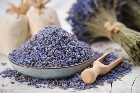 Blue plate of dried lavender. Wooden scoop of dry lavender flowers. Lavender bouquet and sachets on background.