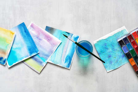 Set of paper sheets of watercolor patterns, glass of water, brush for painting and watercolor paints. Top view.