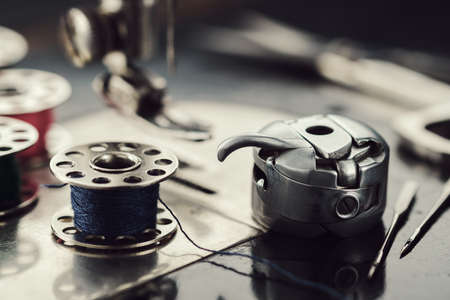 Working part of antique sewing machine. Selective focus on spool of thread, metal shuttle and sewing needles.