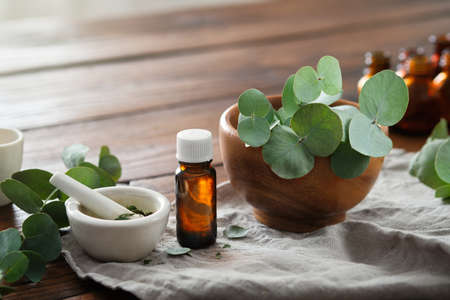 Bottle of eucalyptus oil, mortar and wooden bowl of green eucalyptus leaves. Фото со стока