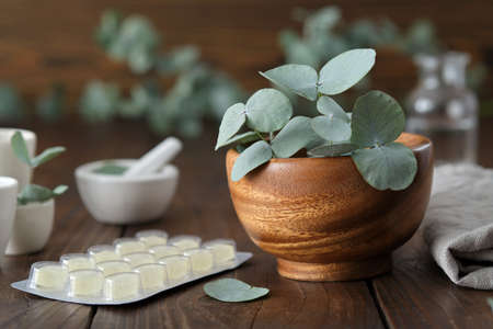 Wooden mortar of green eucalyptus leaves and lozengers for care sore throat and cough.