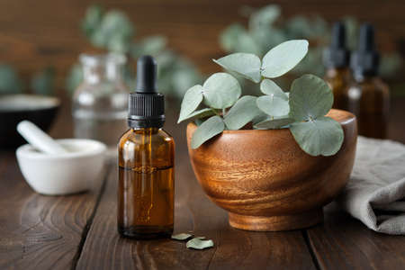 Dropper bottle of eucalyptus essential oil and wooden bowl of green eucalyptus leaves. Mortar and oil bottles on background, not in focus. Фото со стока