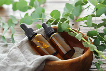 Two bottles of eucalyptus essential oil in wooden bowl and eucalyptus twigs on table. Alternative medicine.