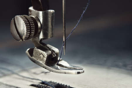 Close up of sewing machine needle with thread. Working part of antique sewing machine. Фото со стока