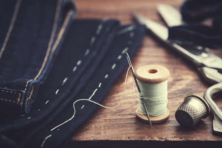 Shortening jeans. Wooden spool of thread, thimble and scissors on table. Jeans cutting. Standard-Bild